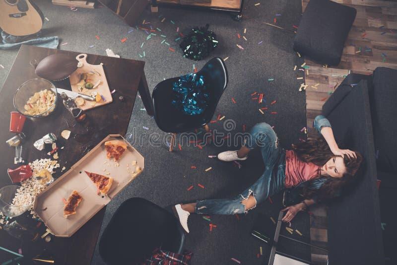 Νέα πιωμένη γυναίκα που βρίσκεται στο πάτωμα στο ακατάστατο δωμάτιο στοκ εικόνες