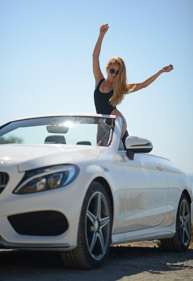 Νέα προκλητική γυναίκα στο άσπρο αυτοκίνητο καμπριολέ στις καλοκαιρινές διακοπές ευτυχείς στοκ φωτογραφία με δικαίωμα ελεύθερης χρήσης