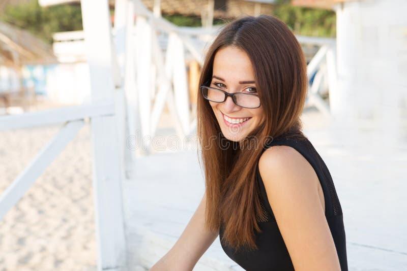 Νέα προκλητική γυναίκα σπουδαστής στα γυαλιά ανάγνωσης στοκ φωτογραφίες