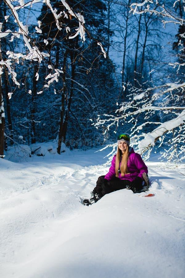 Νέα προκλητική συνεδρίαση γυναικών στο σνόουμπορντ της στο χειμερινό δάσος στοκ εικόνες