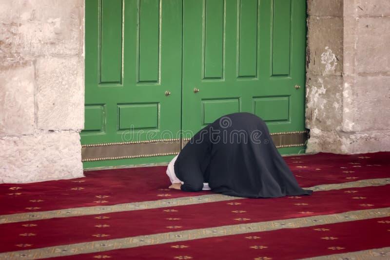 Νέα προσευμένος γυναίκα που αφορά τα γόνατα ενάντια στο θόλο μουσουλμανικών τεμενών του βράχου στο μουσουλμανικό τέταρτο της παλα στοκ φωτογραφίες