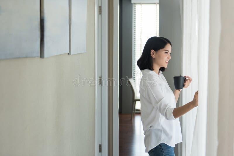 Νέα πρότυπη στάση γυναικών κοντά στο παράθυρο με ένα φλιτζάνι του καφέ στοκ φωτογραφίες
