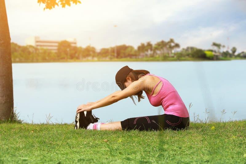 Νέα πόδια τεντώματος συνεδρίασης δρομέων γυναικών ικανότητας πριν από το τρέξιμο επάνω στοκ εικόνες