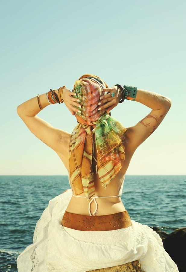 Νέα πλάτη γυναικών μόδας, συνεδρίαση κοριτσιών σε μια πέτρα ενάντια seascape στοκ εικόνα