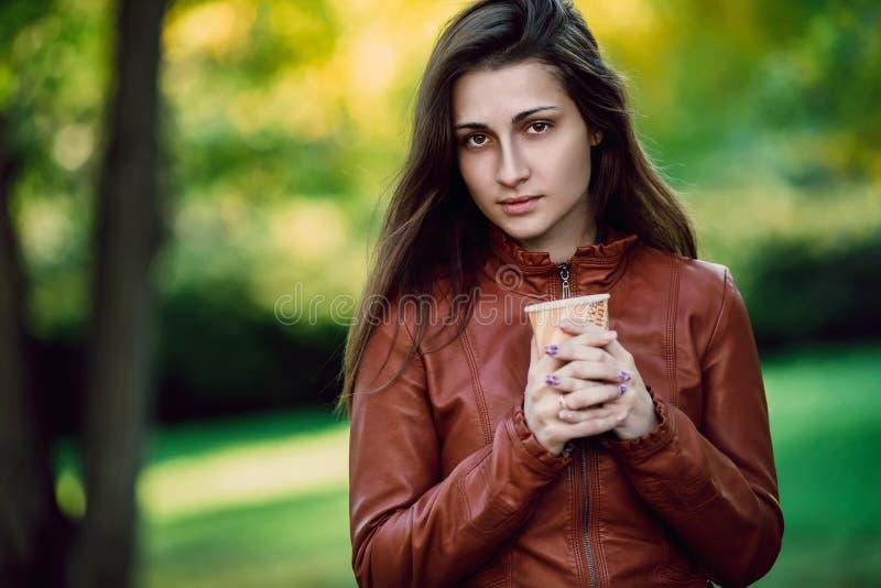Νέα ρομαντική γυναίκα στο καφετί σακάκι δέρματος πέρα από το πορτρέτο φθινοπώρου υποβάθρου Όμορφη τοποθέτηση κοριτσιών στο πάρκο  στοκ φωτογραφία με δικαίωμα ελεύθερης χρήσης