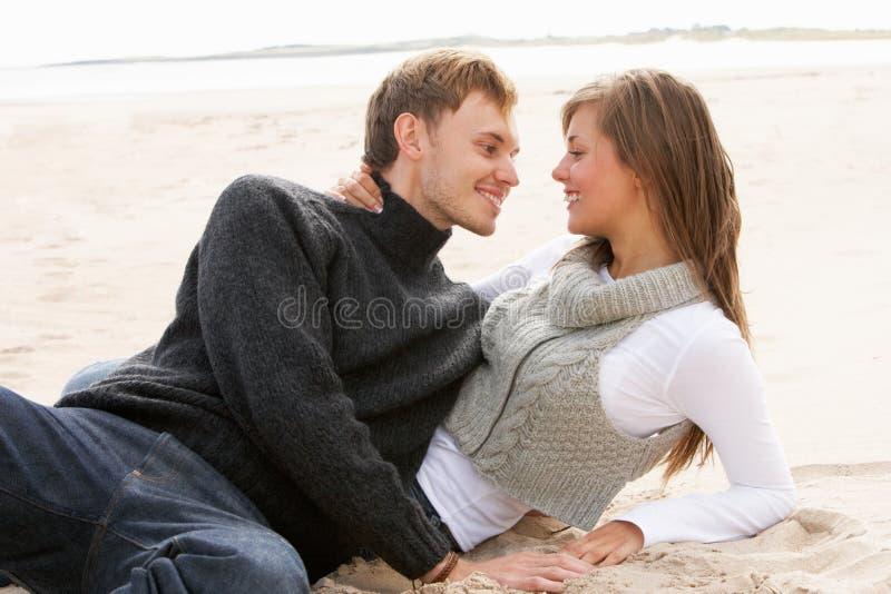 Νέα ρομαντική χαλάρωση ζεύγους στην παραλία από κοινού στοκ φωτογραφίες με δικαίωμα ελεύθερης χρήσης