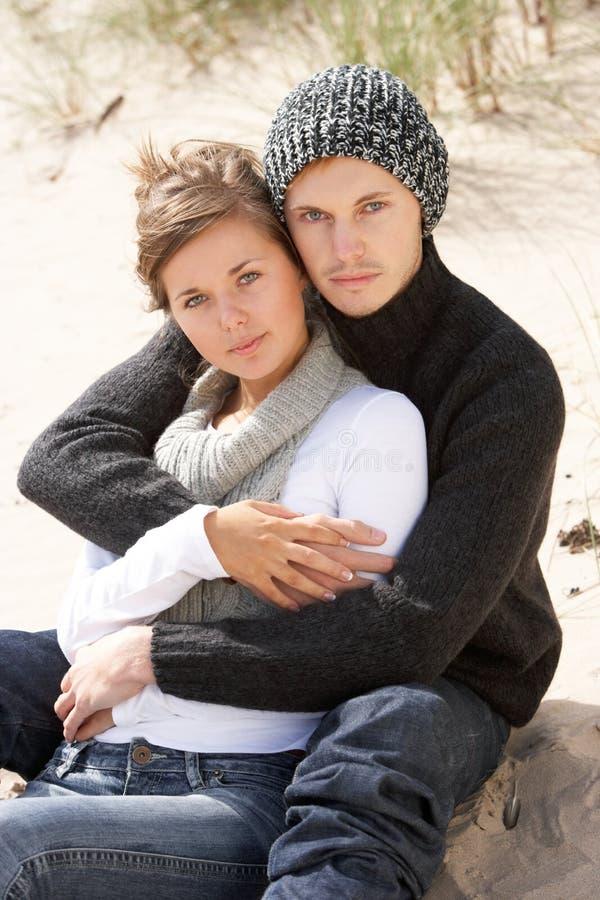 Νέα ρομαντική χαλάρωση ζεύγους στην παραλία από κοινού στοκ φωτογραφία με δικαίωμα ελεύθερης χρήσης