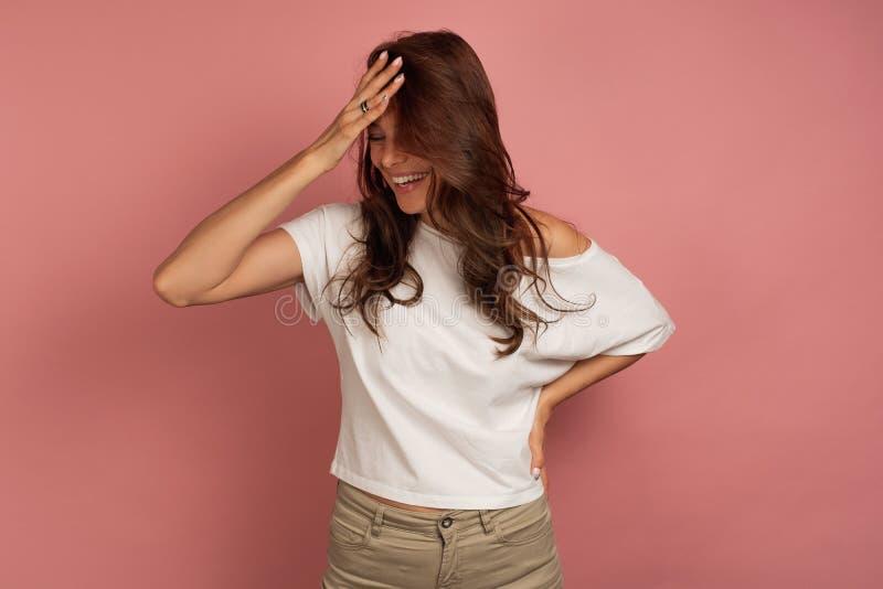 Νέα σκοτεινός-μαλλιαρή γυναίκα γέλια στα άσπρα μπλουζών που βάζει το χέρι της στο μέτωπό της, ρόδινο υπόβαθρο στοκ εικόνα