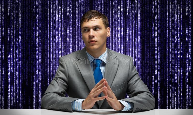 Νέα σοβαρά διπλωμένα άτομο χέρια και συνεδρίαση στο γραφείο στοκ φωτογραφίες