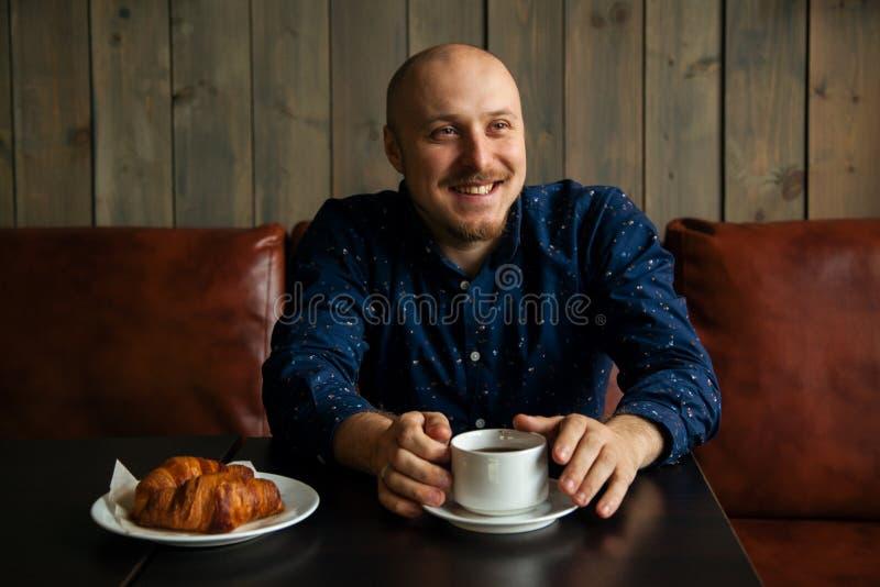 Νέα σοβαρή μοντέρνη συνεδρίαση ατόμων μόνο στον σοφίτα-ορισμένο καφέ στοκ φωτογραφία