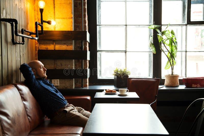 Νέα σοβαρή μοντέρνη συνεδρίαση ατόμων μόνο στον σοφίτα-ορισμένο καφέ στοκ εικόνες