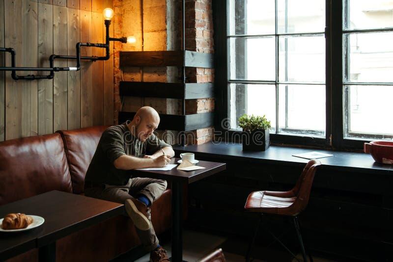 Νέα σοβαρή μοντέρνη συνεδρίαση ατόμων μόνο στον σοφίτα-ορισμένο καφέ στοκ εικόνα