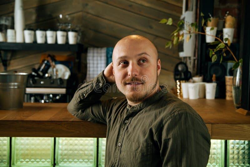 Νέα σοβαρή μοντέρνη συνεδρίαση ατόμων μόνο στον σοφίτα-ορισμένο καφέ στοκ εικόνα με δικαίωμα ελεύθερης χρήσης