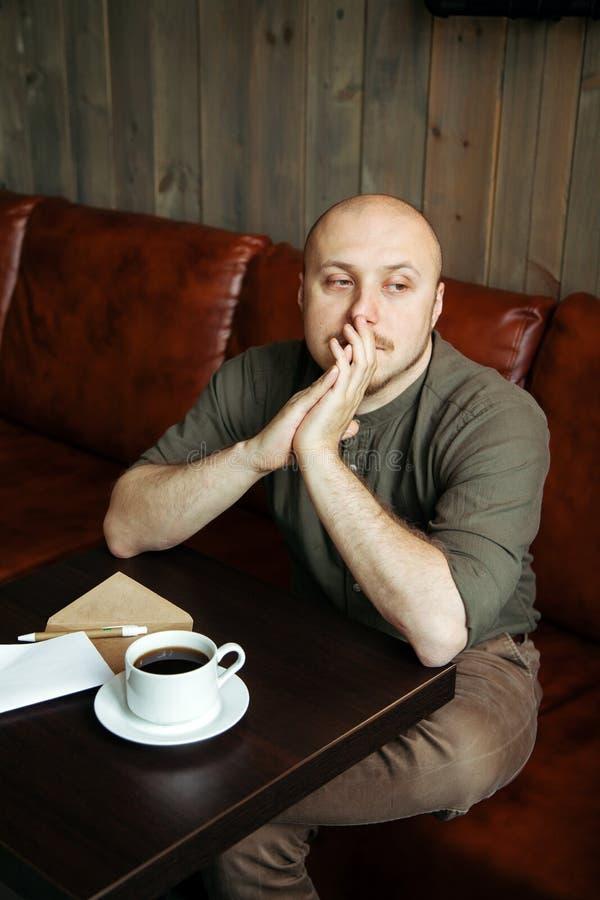 Νέα σοβαρή μοντέρνη συνεδρίαση ατόμων μόνο στον σοφίτα-ορισμένο καφέ στοκ φωτογραφία με δικαίωμα ελεύθερης χρήσης