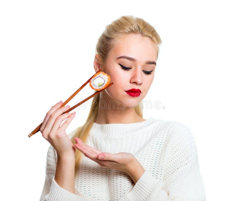 Νέα σούσια εκμετάλλευσης γυναικών με chopsticks, που απομονώνονται στο λευκό στοκ εικόνες