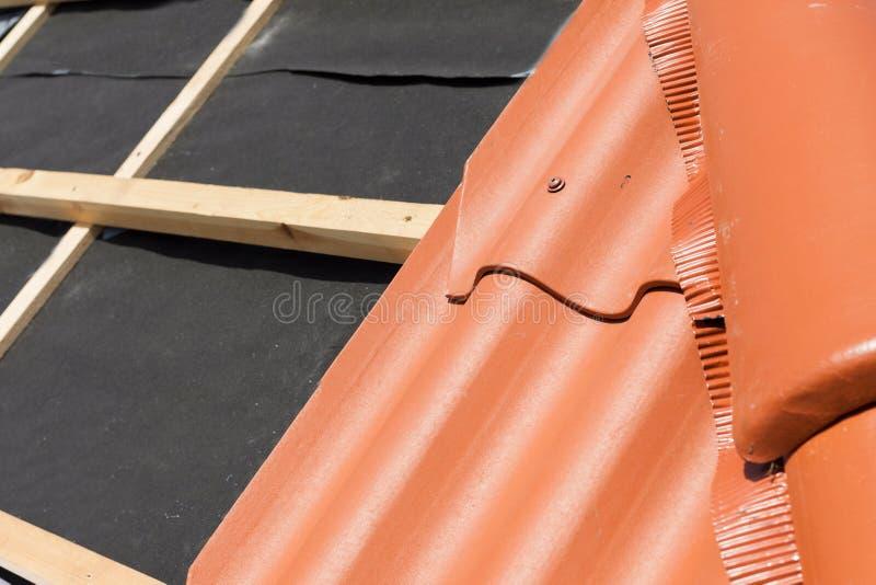 Νέα στέγη κάτω από την κατασκευή με τις ξύλινες ακτίνες, το στρώμα στεγανοποίησης για τη γωνία και το φυσικό κεραμίδι στοκ φωτογραφία με δικαίωμα ελεύθερης χρήσης