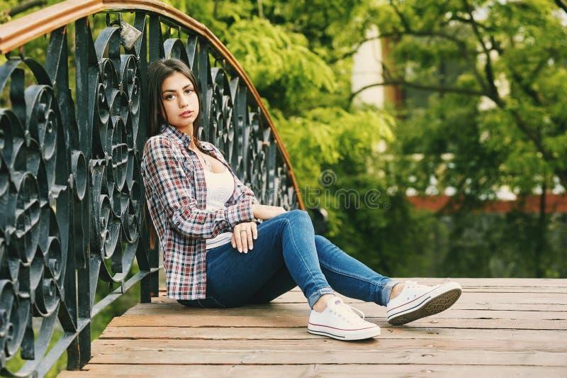 Νέα στηργμένος συνεδρίαση γυναικών σε μια ξύλινη γέφυρα στοκ φωτογραφία με δικαίωμα ελεύθερης χρήσης