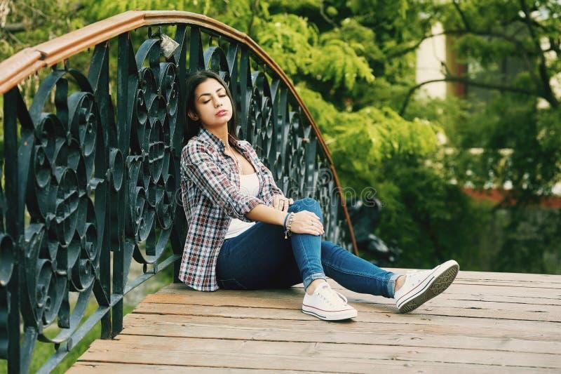 Νέα στηργμένος συνεδρίαση γυναικών σε μια ξύλινη γέφυρα στοκ φωτογραφίες με δικαίωμα ελεύθερης χρήσης