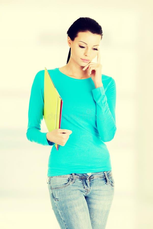 Νέα στοχαστική γυναίκα με τις σημειώσεις της στοκ φωτογραφία με δικαίωμα ελεύθερης χρήσης