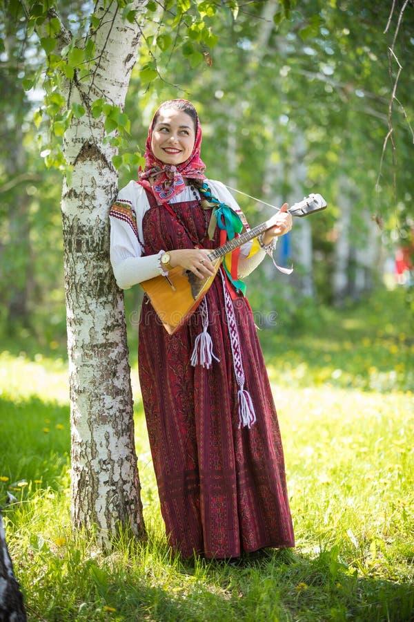 Νέα στοχαστική γυναίκα στα παραδοσιακά ρωσικά ενδύματα που στέκονται στο δάσος και που κρατούν το balalaika στοκ εικόνα με δικαίωμα ελεύθερης χρήσης
