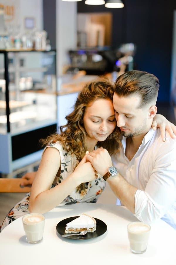 Νέα συμπαθητική συνεδρίαση ζευγών στον καφέ με τα φλυτζάνια του coffe, του κέικ και του αγκαλιάσματος στοκ φωτογραφίες