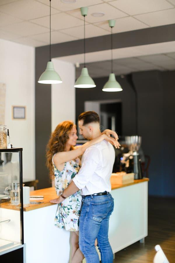 Νέα συμπαθητική σύζυγος που αγκαλιάζει το σύζυγο στον καφέ στοκ φωτογραφία