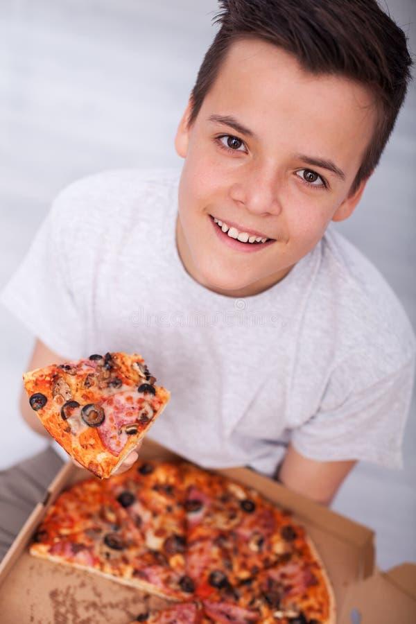 Νέα συνεδρίαση αγοριών εφήβων στο πάτωμα με ένα κιβώτιο της πίτσας στοκ φωτογραφία με δικαίωμα ελεύθερης χρήσης