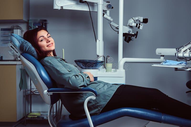 Νέα συνεδρίαση γυναικών σε μια καρέκλα σε ένα γραφείο οδοντιάτρων στοκ εικόνες με δικαίωμα ελεύθερης χρήσης