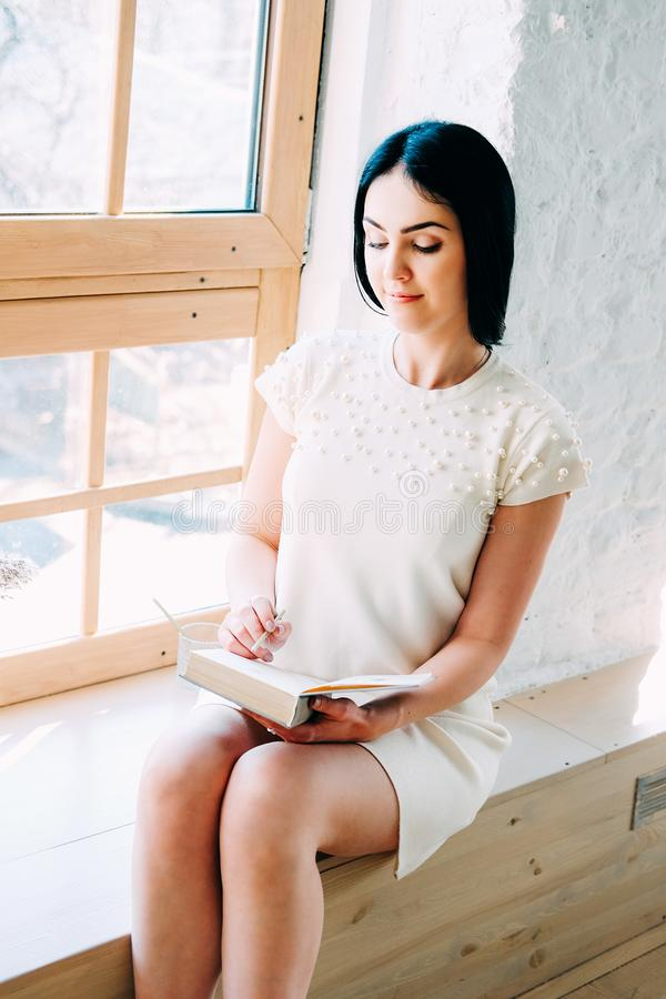 Νέα συνεδρίαση γυναικών σπουδαστών στην κατηγορία που διαβάζει ένα βιβλίο στοκ φωτογραφίες