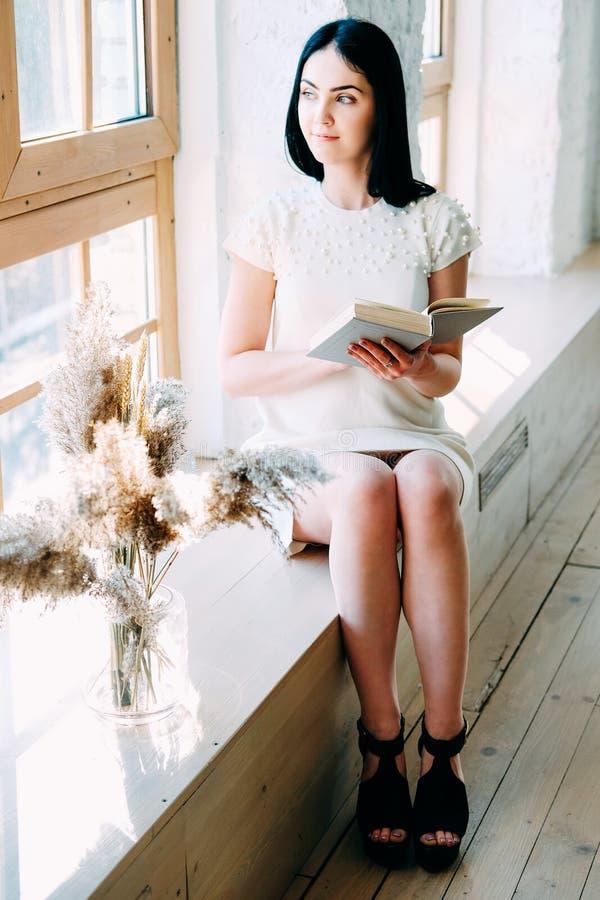Νέα συνεδρίαση γυναικών σπουδαστών στην κατηγορία που διαβάζει ένα βιβλίο στοκ εικόνες