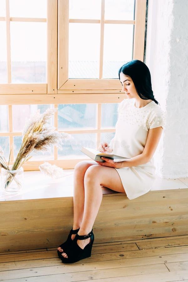Νέα συνεδρίαση γυναικών σπουδαστών στην κατηγορία που διαβάζει ένα βιβλίο στοκ εικόνα