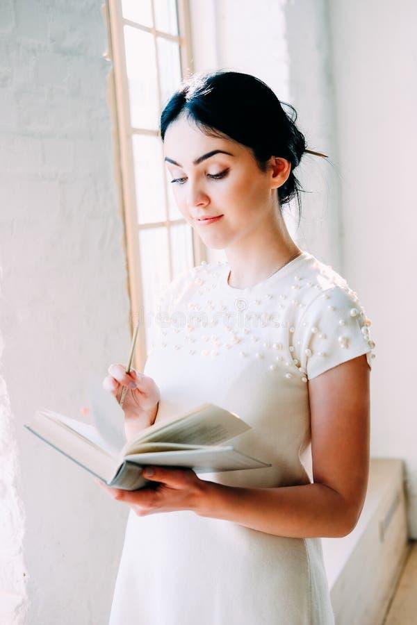 Νέα συνεδρίαση γυναικών σπουδαστών στην κατηγορία που διαβάζει ένα βιβλίο στοκ φωτογραφία με δικαίωμα ελεύθερης χρήσης
