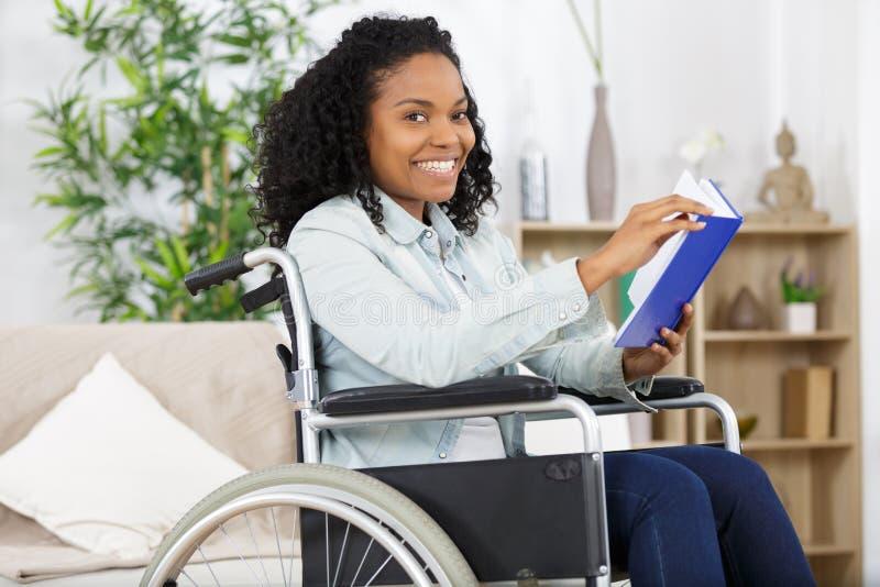 Νέα συνεδρίαση γυναικών στην αναπηρική καρέκλα βιβλίο ανάγνωσης στοκ εικόνες