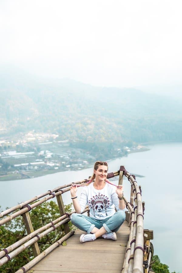 Νέα συνεδρίαση γυναικών στην ξύλινη γέφυρα στην κορυφή του βουνού με ένα τροπικό υπόβαθρο λιμνών Νησί του Μπαλί στοκ φωτογραφίες