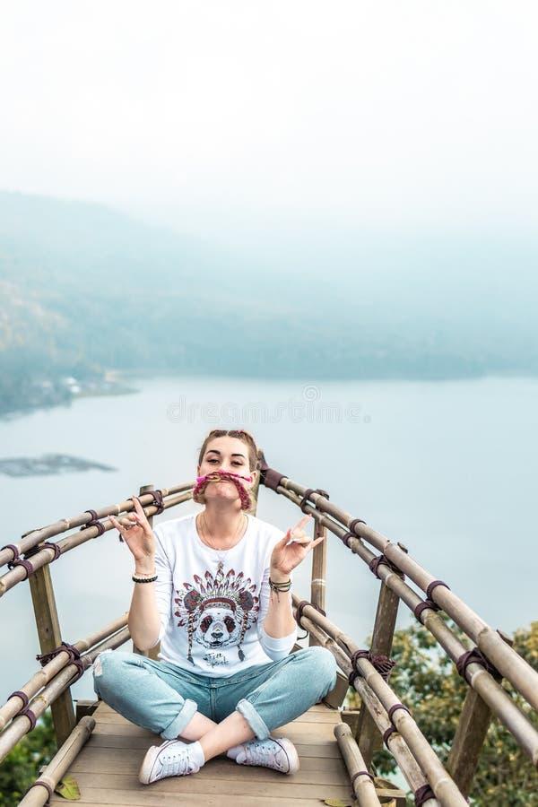Νέα συνεδρίαση γυναικών στην ξύλινη γέφυρα στην κορυφή του βουνού με ένα τροπικό υπόβαθρο λιμνών Νησί του Μπαλί στοκ εικόνα