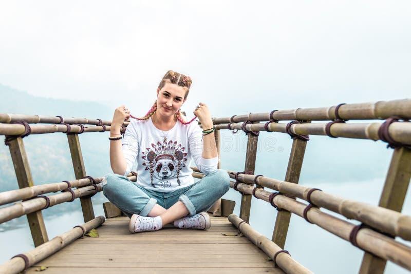 Νέα συνεδρίαση γυναικών στην ξύλινη γέφυρα στην κορυφή του βουνού με ένα τροπικό υπόβαθρο λιμνών Νησί του Μπαλί στοκ εικόνες