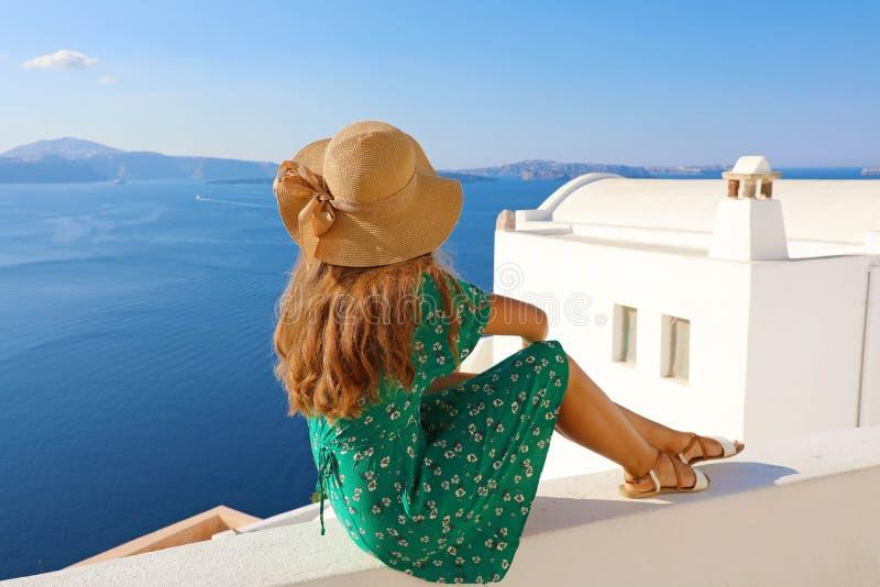 Νέα συνεδρίαση γυναικών στον τοίχο και κοίταγμα στο όμορφο τοπίο σε Santorini, Ελλάδα απομονωμένο οπισθοσκόπο λευκό στοκ φωτογραφία