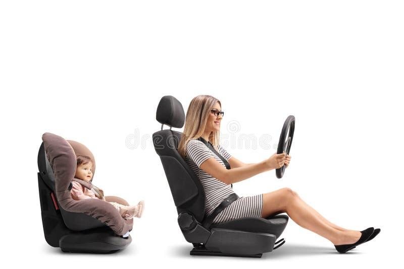 Νέα συνεδρίαση γυναικών στο κάθισμα αυτοκινήτων και το τρυπώντας τιμόνι στοκ εικόνες