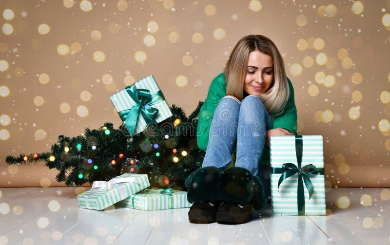 Νέα συνεδρίαση γυναικών στο πάτωμα κοντά στο χριστουγεννιάτικο δέντρο έλατου και να ονειρευτεί για τα παρόντα, μελλοντικά, δώρα κ στοκ εικόνες