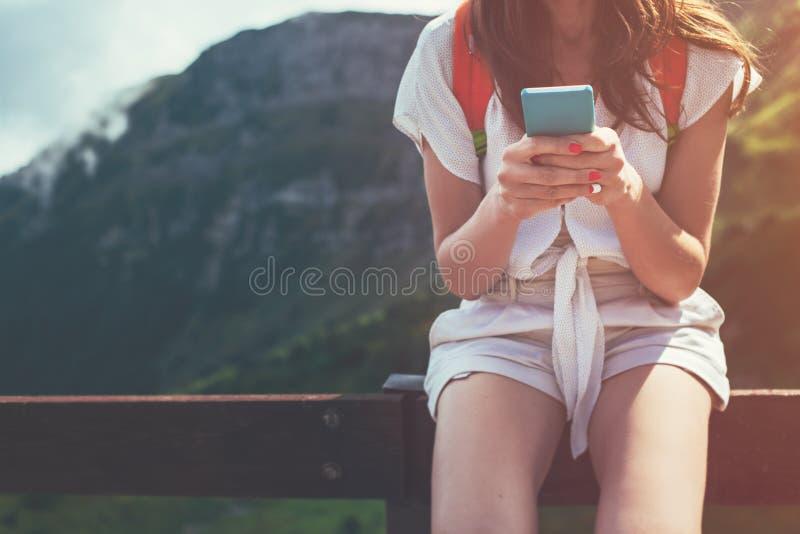 Νέα συνεδρίαση γυναικών στο φράκτη με το smartphone Τουριστική πορεία υψηλών βουνών Ψηφιακή επικοινωνία Texting με τους φίλους στοκ εικόνες