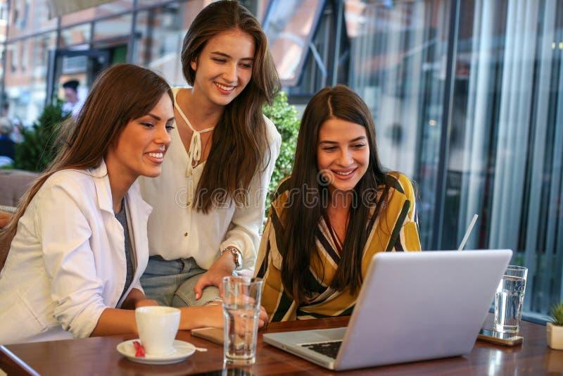 Νέα συνεδρίαση γυναικών τρία στον καφέ που χρησιμοποιεί το lap-top στοκ φωτογραφίες