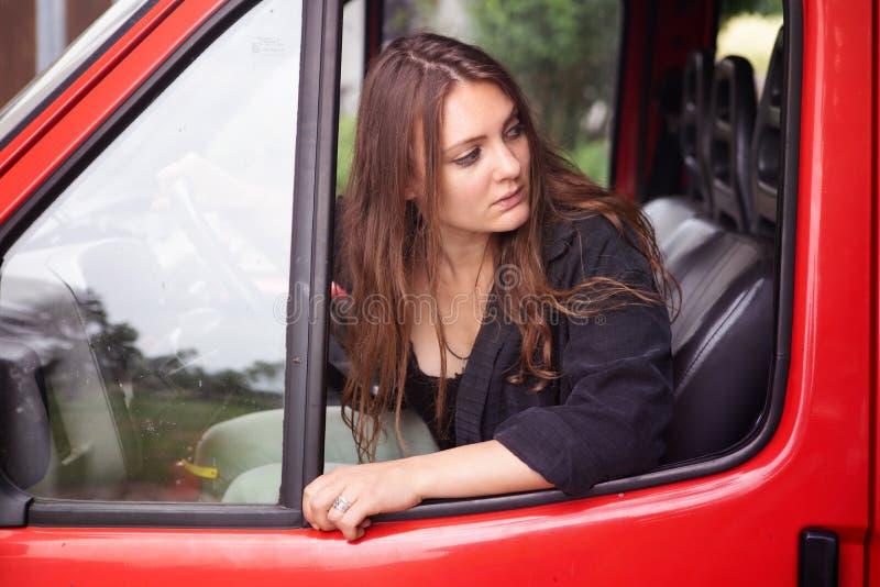 Νέα συνεδρίαση γυναικών brunette στο αυτοκίνητο και οδήγηση προς τα πίσω στοκ εικόνες με δικαίωμα ελεύθερης χρήσης