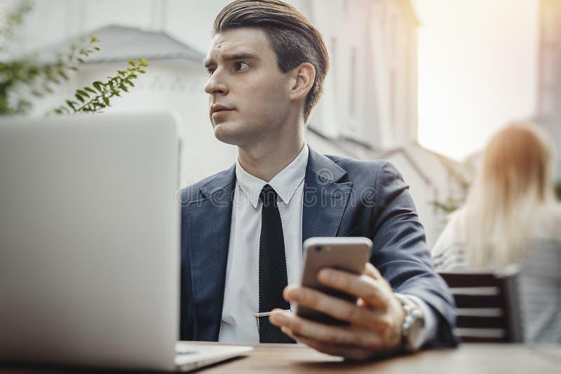Νέα συνεδρίαση επιχειρηματιών δίπλα στο κινητό τηλέφωνο lap-top και εκμετάλλευσης υπό εξέταση στοκ φωτογραφία με δικαίωμα ελεύθερης χρήσης