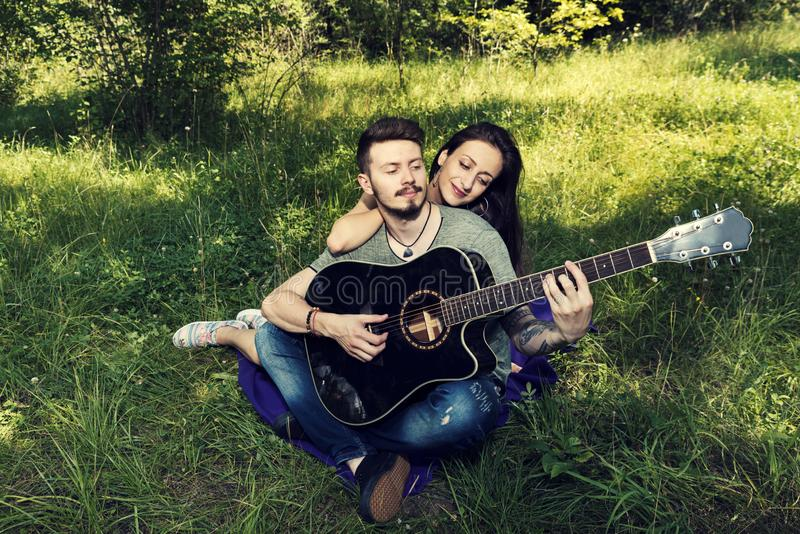 Νέα συνεδρίαση ζευγών κάτω σε ένα πορφυρό κάλυμμα και παιχνίδι σε μια κιθάρα στοκ φωτογραφία με δικαίωμα ελεύθερης χρήσης