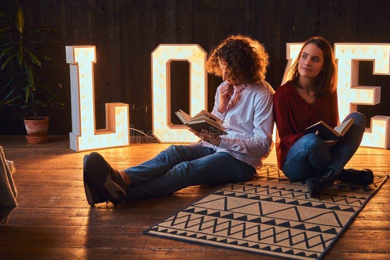 Νέα συνεδρίαση ζευγών σπουδαστών σε ένα πάτωμα και ανάγνωση μαζί σε ένα δωμάτιο που διακοσμείται με τις ογκώδεις επιστολές με στοκ φωτογραφία με δικαίωμα ελεύθερης χρήσης