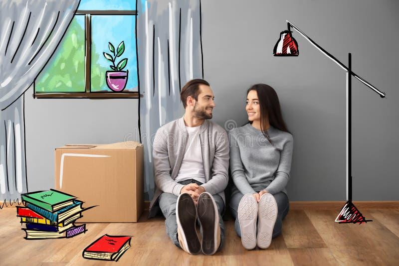 Νέα συνεδρίαση ζευγών στο πάτωμα κοντά στο κιβώτιο στο εσωτερικό και φανταμένος το εσωτερικό του καινούργιου σπιτιού Κινούμενη ημ στοκ φωτογραφίες με δικαίωμα ελεύθερης χρήσης