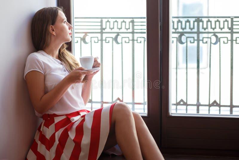 Νέα συνεδρίαση καφέ κατανάλωσης γυναικών κοντά στο μπαλκόνι στοκ εικόνες με δικαίωμα ελεύθερης χρήσης
