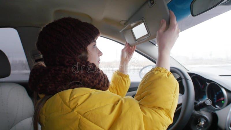 Νέα συνεδρίαση οδηγών γυναικών στο αυτοκίνητο και κοίταγμα στον καθρέφτη στοκ φωτογραφία με δικαίωμα ελεύθερης χρήσης