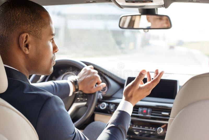 Νέα συνεδρίαση οδηγών επιχειρηματιών μέσα στο αυτοκίνητο που εξετάζει κατά μέρος σχετική την οχήματα άποψη πίσω θέσεων στοκ φωτογραφία