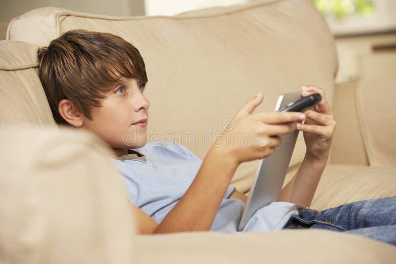Νέα συνεδρίαση αγοριών στον καναπέ που χρησιμοποιεί στο σπίτι τον υπολογιστή ταμπλετών ταυτόχρονα προσέχοντας την τηλεόραση στοκ εικόνες